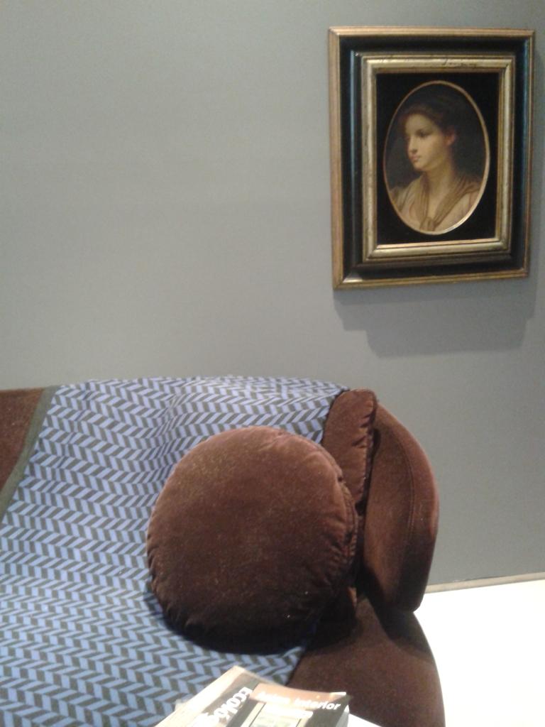 """Montagem de quadro e sofá com desenho e """"personalidade"""" forte em parede cinza (neutra)"""
